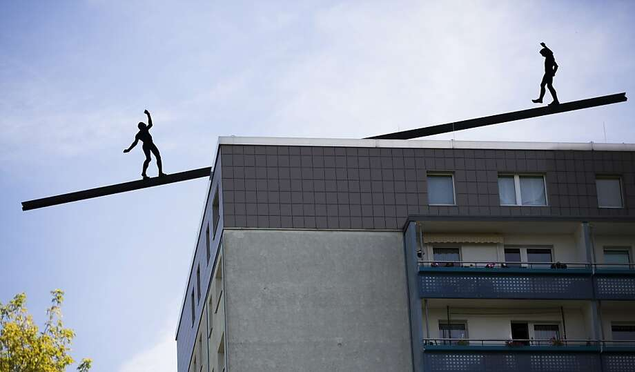 "The Wallendas must be in town: Aluminum figures ""balance"" on a beam placed on a Berlin 