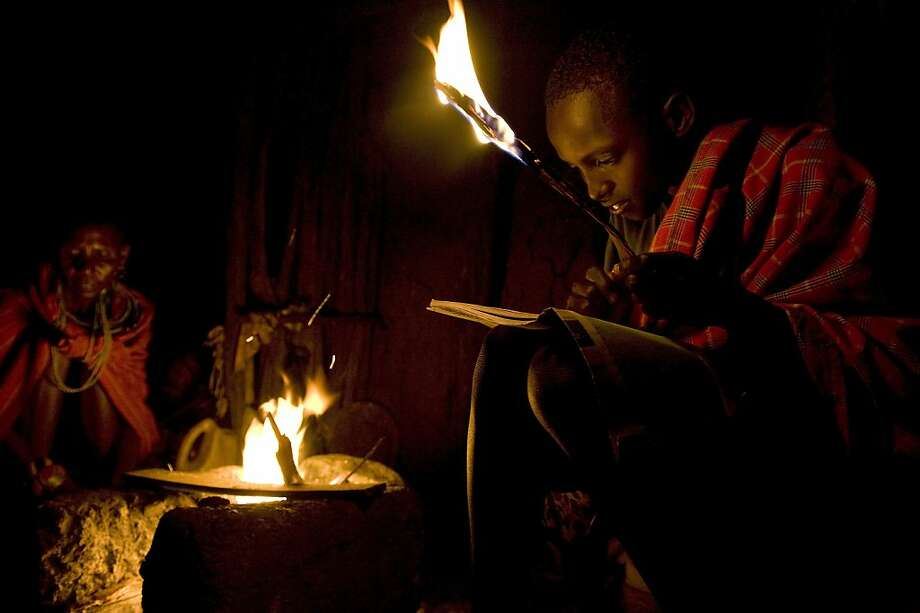 TOPSHOTS Kelvin Leadismo,12, is doing his homework by a firelight in his family's manyatta (traditional home plastered with cowdung) with his siblings on July 16, 2013  in Kisima township of Kenya's nothern county of Samburu. The class is attended by young shepherds from the Samburu community who are usually unable to attend regular daytime classes when they are tending to their family's livestock at pasture. The school runs a parallel tuition programme to the national curriculum that enables the otherwise illeterate shepherds acquire literacy through the two to three hour tuition courses presided over by volunteer teachers.  AFP PHOTO / Tony KARUMBATONY KARUMBA/AFP/Getty Images Photo: Tony Karumba, AFP/Getty Images