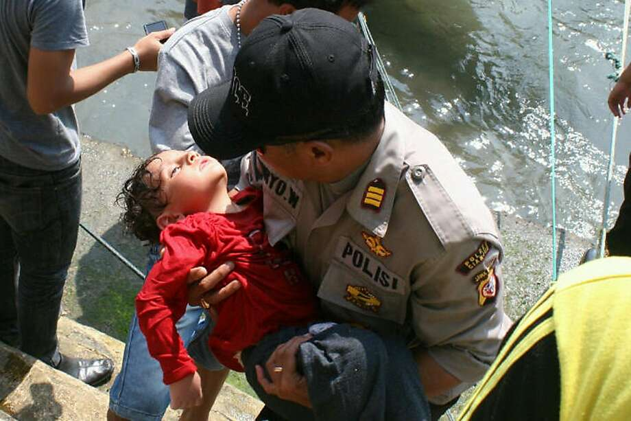 Saved after boat sinks: A police officer carries an exhausted young boy, one of 157 people rescued after their 