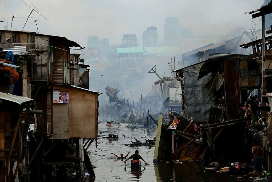 Shantytown burns:Residents searching for salvageable materials wade through water after a fire razed a 