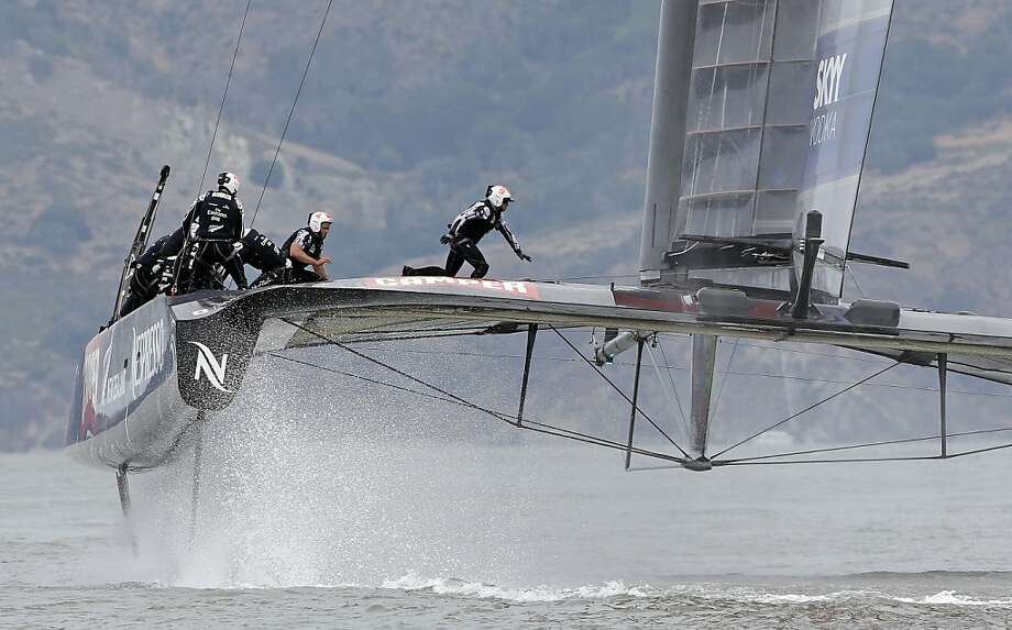 That's one way to trim a cat: Crewmen aboard the Emirates Team New Zealand maneuver the catamaran during an America's Cup race against Italy's Luna Rossa Challenge in San Francisco. The Kiwis won the match. Photo: Eric Risberg, Associated Press