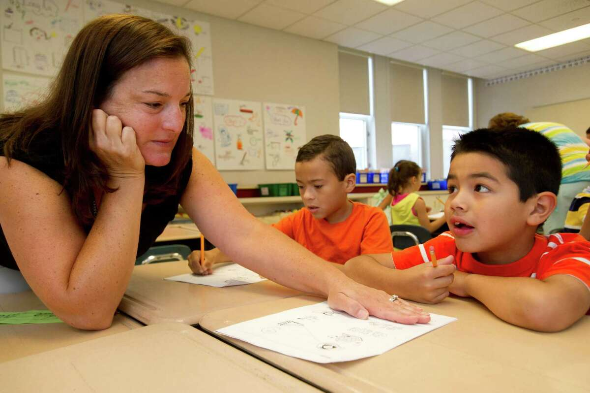 Teacher Toni Fox helps Carlos Santiago with a worksheet during her first-grade summer school class at Julia A. Stark Elementary School in Stamford, Conn., on Wednesday, July 24, 2013.