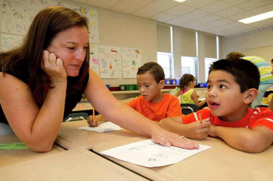 Teacher Toni Fox helps Carlos Santiago with a worksheet during her first-grade summer school class at Julia A. Stark Elementary School in Stamford, Conn., on Wednesday, July 24, 2013. Photo: Lindsay Perry / Stamford Advocate