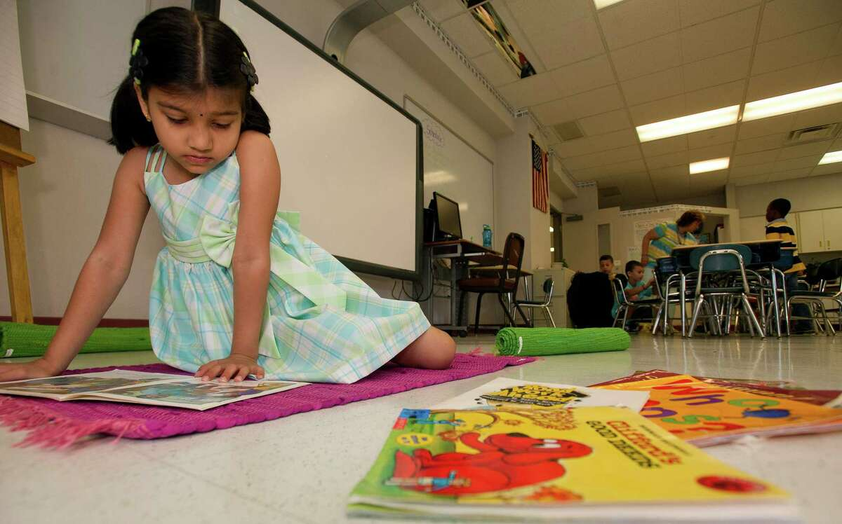 Snigdha Kolachina reads books during Toni Fox's first-grade summer school class at Julia A. Stark Elementary School in Stamford, Conn., on Wednesday, July 24, 2013.