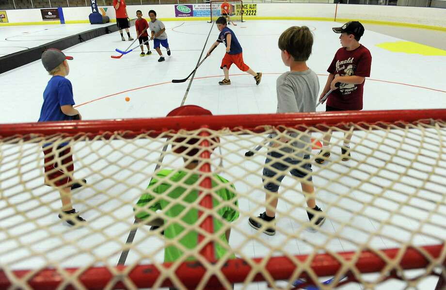 "Kids play floor hockey on the new ""Sport Court"" at the Bethlehem YMCA Tuesday afternoon, July 23, 2013, in Delmar, N.Y. This unique court is the only one in Northeastern N.Y., and is comprised of more than 17,000 individual, modular tiles that were assembled on top of the concrete floor after the ice was removed from the rink in the spring. Kids attending the Bethlehem Y summer camp with make use of this large playing surface. (Lori Van Buren / Times Union) Photo: Lori Van Buren / 00023286A"