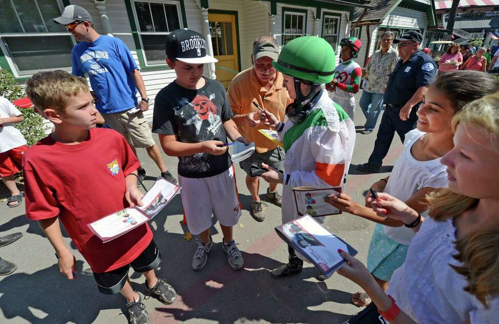 Jockey Rose Napravnik is surrounded by autograph hunters Sept. 2, 2012, at Saratoga Race Course in Saratoga Springs, N.Y. Sept. 2, 2012. (Skip Dickstein/Times Union)
