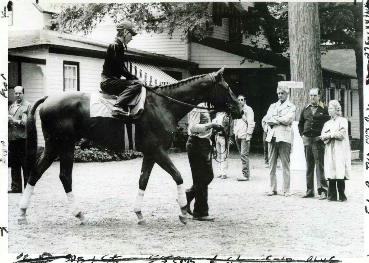 Affirmed, the last Triple Crown winner, is led towards the track on Aug. 6, 1978. He is being watched at the right by owner Louis Wolfson, trainer Laz Barrera and owner Patrice Wolfson.