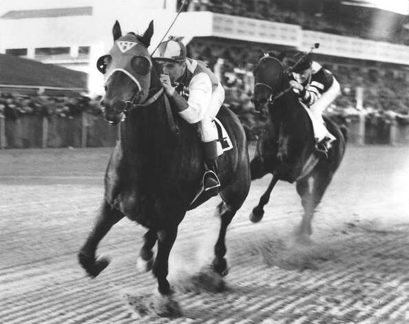 Seabiscuit and jockey George Woolf lead War Admiral and jockey Charles Kurtsinger in the first turn at the race at Pimlico i
