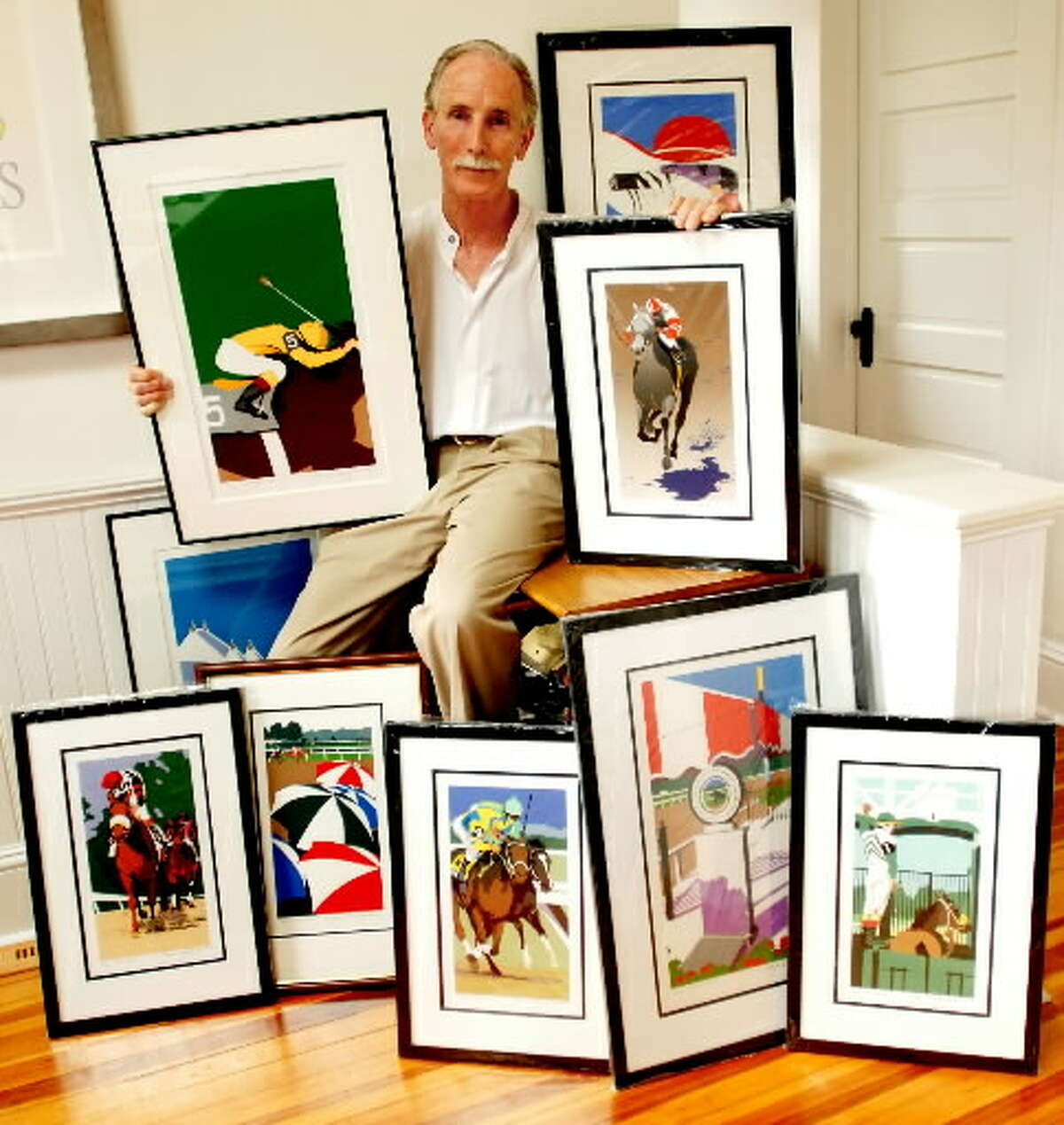 Greg Montgomery posing with some of his Travers postrees (Luanne M. Ferris - Times Union)