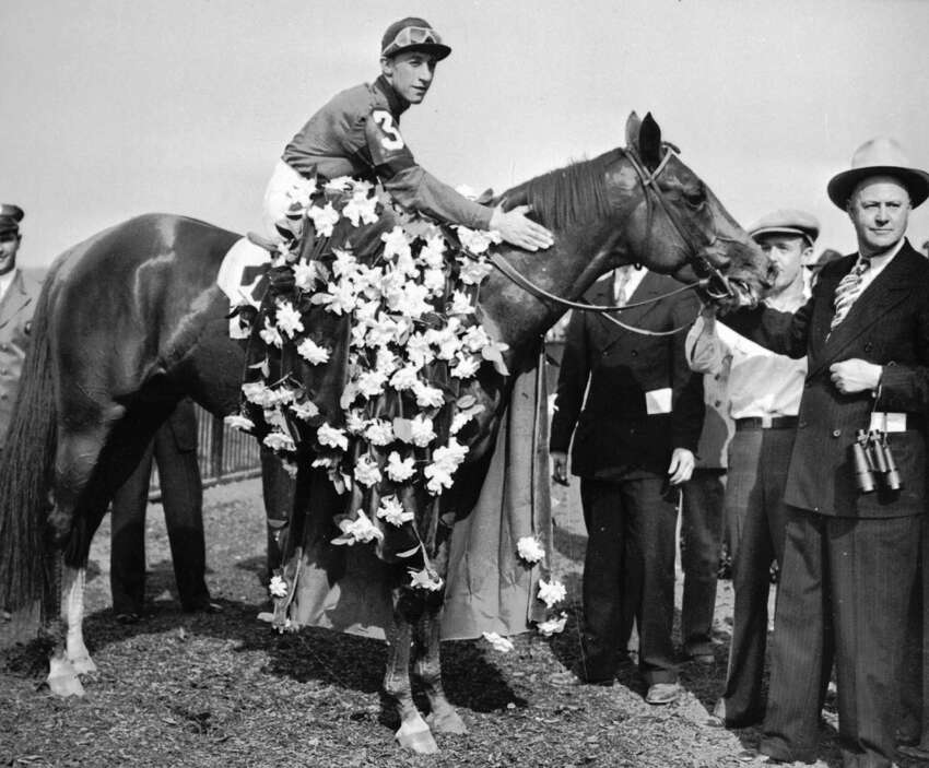 Whirlaway is draped with the floral tribute in the winner's circle at Belmont Park, N.Y., on June 7, 194, after winning the Belmont Stakes race of the Triple Crown with jockey Eddie Arcaro. Trainer Ben Jones holds the bridle. (AP Photo)