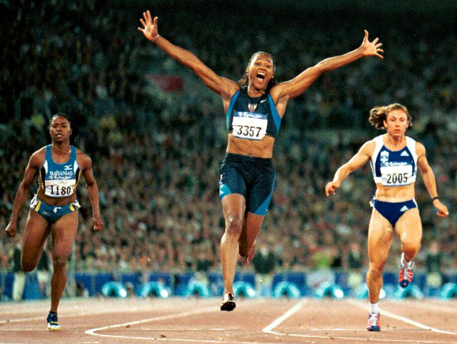 Marion Jones of the United States (center), celebrating her victory in the 100 meters in the 2000 Olympics in Sydney, had gold medals stripped because of doping. Photo: DOUG MILLS, AP / AP
