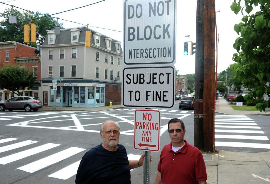 Shelton Aldermen Stanley Kudej, left, and Eric McPherson stand at the intersection of Howe Avenue and Center Street in downtown Shelton, Conn. Tuesday, July 23, 2013 near a newly-installed sign that warns of fines for blocking the intersection. Photo: Autumn Driscoll / Connecticut Post