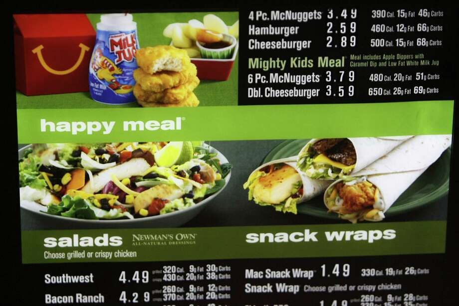 Calorie, fat and carb counts are seen on the menu board at a McDonald's restaurant. The jury is still out on whether posting the information will change consumer behavior. Photo: Julio Cortez / Houston Chronicle