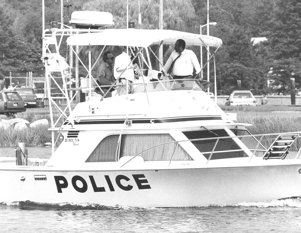 Stamford Health Director Dr. Andrew McBride, in a shirt and tie, rides in a police boat in search of water-borne waste on Aug. 3, 1988.