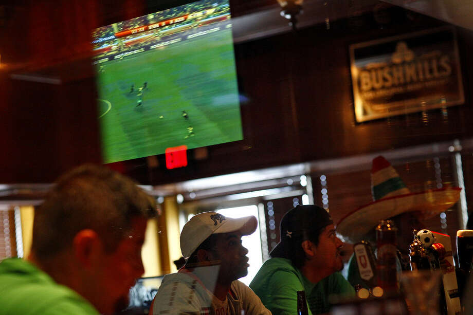 Soccer fans take in a match at the British-themed pub The Lion & Rose. Photo: Express-News File Photo