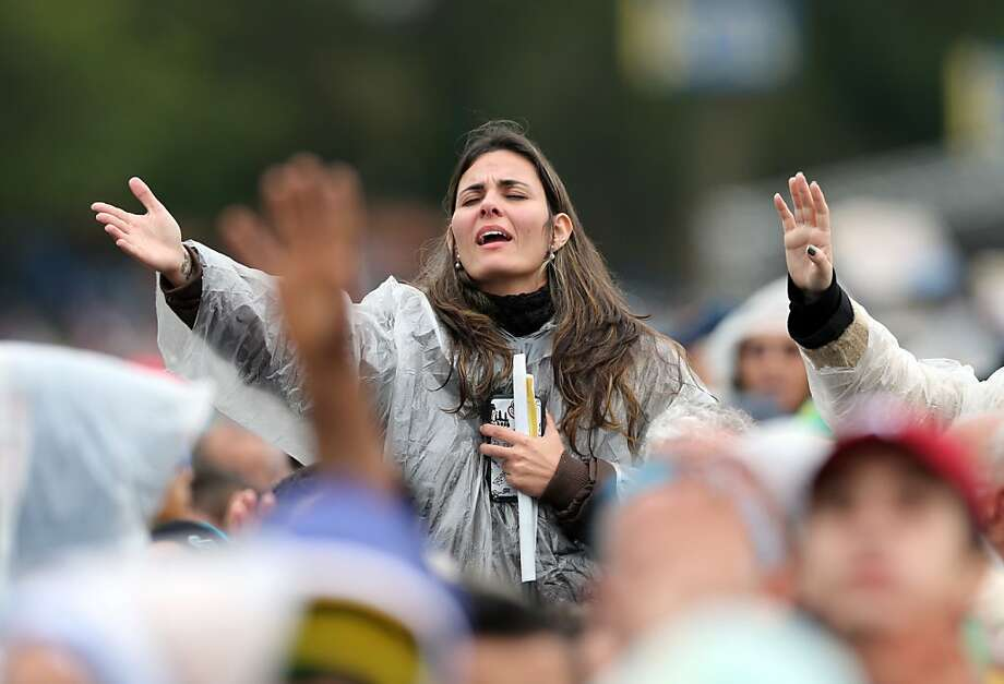 A woman prays during a Mass celebrated by Pope Francis outside the Aparecida Basilica in Aparecida, Brazil, Wednesday, July 24, 2013. Tens of thousands of faithful flocked to the tiny town of Aparecida, tucked into an agricultural region halfway between Rio de Janeiro and Sao Paulo, where he is to celebrate the first public Mass of his trip in a massive basilica dedicated to the nation's patron saint. (AP Photo/Andre Penner) Photo: Andre Penner, Associated Press
