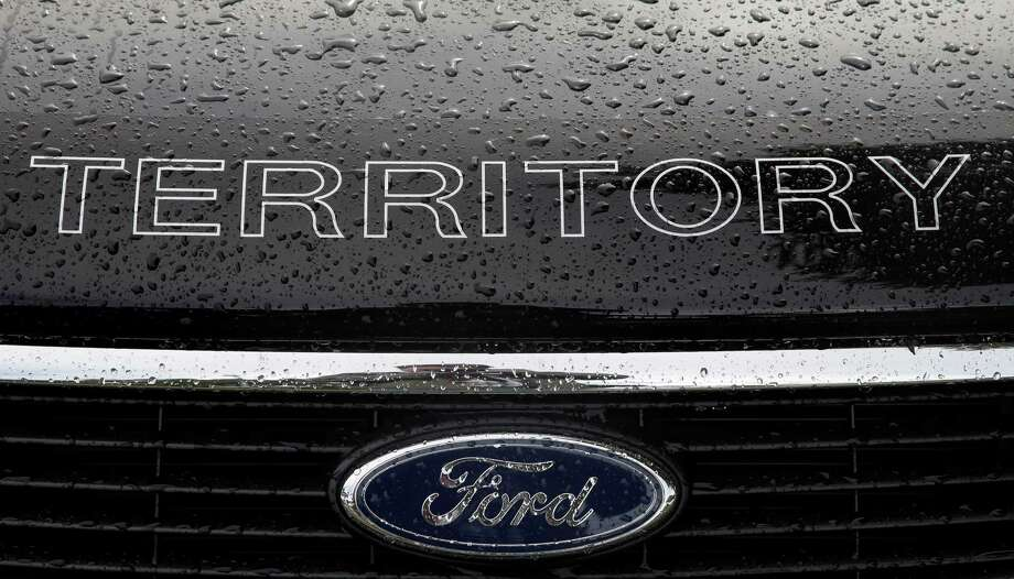 In this Thursday, May 23, 2013, photo, rain falls on a car at a Ford dealership in Sydney, Australia. Ford Motor Co. reports quarterly earnings on Wednesday, July 24, 2013. (AP Photo/Rick Rycroft) ORG XMIT: NYBZ114 Photo: Rick Rycroft / AP