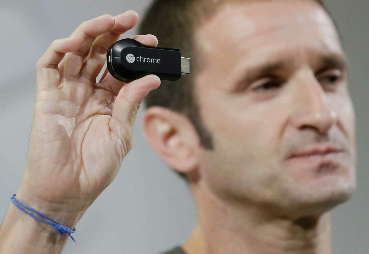 Google's new Chromecast device is shown by Mario Queiroz, vice president for product management, on Wednesday, July 24, 2013, in San Francisco. (AP Photo/Marcio Jose Sanchez) ORG XMIT: CAMS115