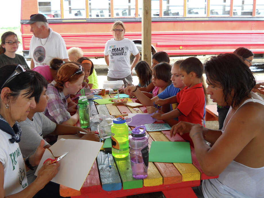 Volunteers from Shelton and Middlebury, Conn., lead young Lakota Sioux children in arts and crafts at Simply Smiles, on the Cheyenne River Reservation in La Plant, S.D., recently. Photo: Bob Moseley