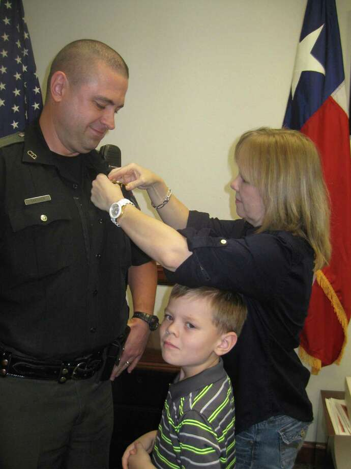 Danel Carriker pins the badge on her newly promoted husband, Sgt. Chris Carriker, as son C.J. looks on. Photo: Courtesy Of Fort Bend County Constables Precinct 4