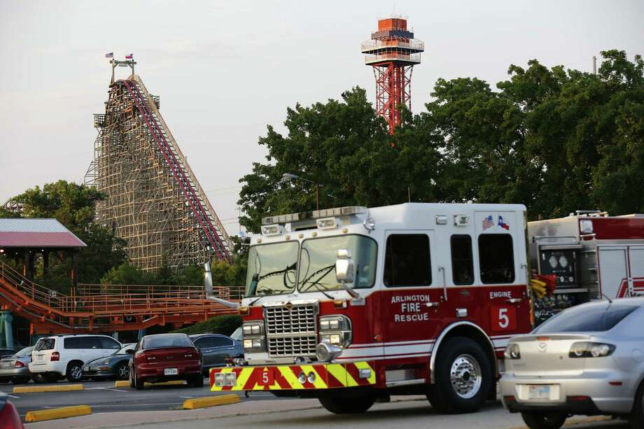Emergency personnel were on the scene at Six Flags Over Texas in Arlington, Texas, after a woman died on the Texas Giant roller coaster (background left) on Friday, July 19, 2013.  Photo: Tom Fox, Associated Press / The Dallas Morning News
