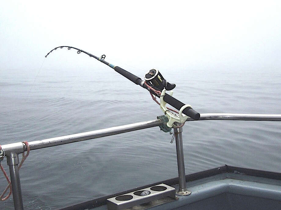 Calm before the storm, a rod sits in holder, as anglers wait for the first bite of the day, trolling for salmon out the Golden Gate Photo: Brian Murphy