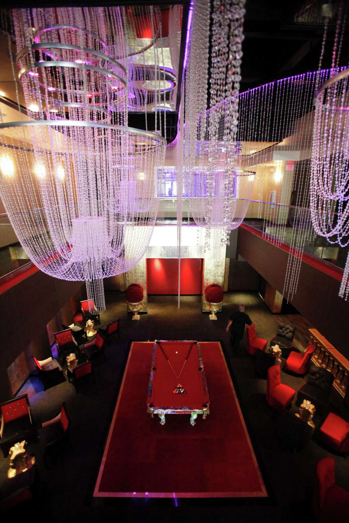 The new Midtown steakhouse and bar Mr. Peeples has a double-height room with large Swarovski crystal chandeliers.