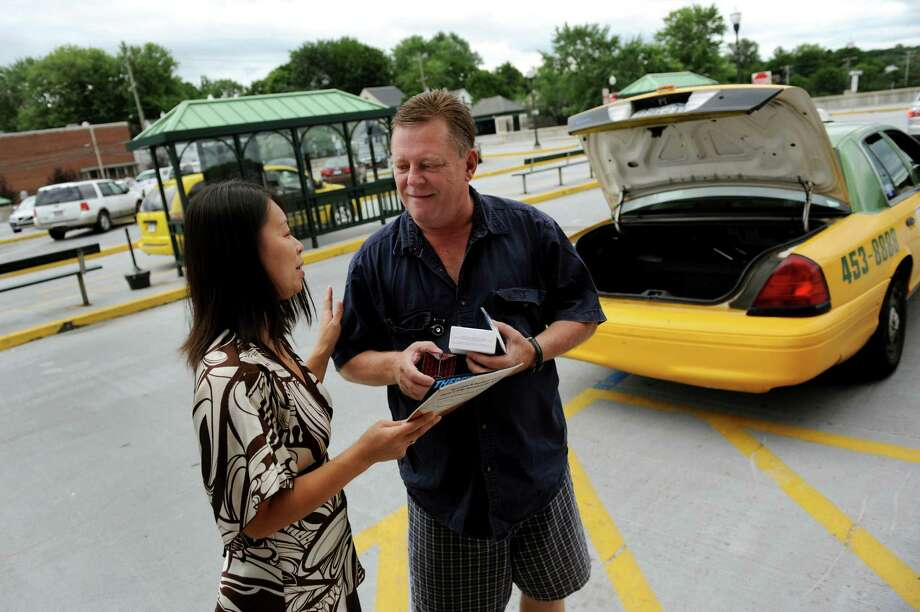 Eddie O'Kane, driver for Capitaland Taxi, center receives gifts from Hiroko Gier of the Residence Inn in East Greenbush on Wednesday, July 24, 2013, at the Rensselaer Train Station in Rensselaer, N.Y. Albany County Convention and Visitors Bureau members thanked cab drivers for being the first point of hospitality with gifts of energy bars, water bottles and fruit at the train station and airport. (Cindy Schultz / Times Union) Photo: Cindy Schultz / 00023271A