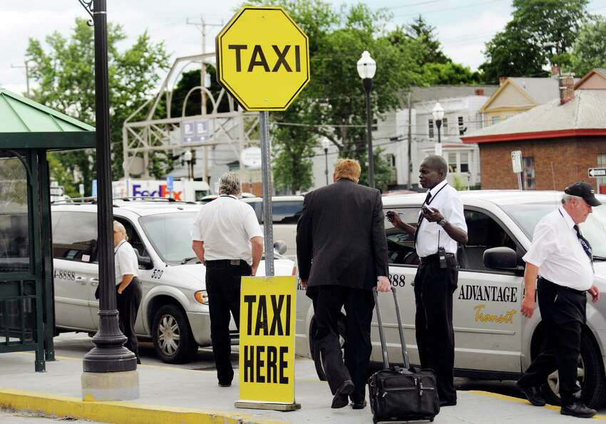 John Debo, cab driver supervisor for Advantage, second from right, assists a traveler on Wednesday, July 24, 2013, at the Rensselaer Train Station in Rensselaer, N.Y. (Cindy Schultz / Times Union)