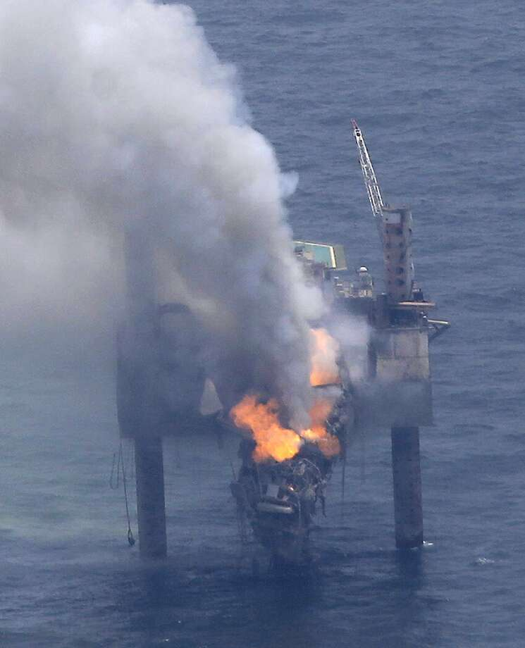 A fire is seen on the Hercules 265 drilling rig in the Gulf of Mexico off the coast of Louisiana, Wednesday, July 24, 2013. Natural gas spewed uncontrolled from the well on Tuesday after a blowout that forced the evacuation of 44 workers aboard the drilling rig, authorities said. No injuries were reported in the blowout. (AP Photo/Gerald Herbert) Photo: Gerald Herbert, Associated Press