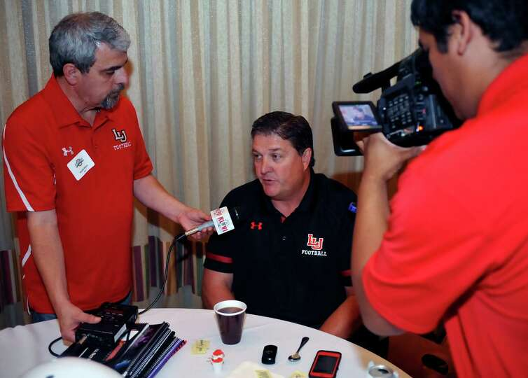 Head Coach Ray Woodard, center, is interviewed by Harold Mann, left, of KLVI radio out of Beaumont.