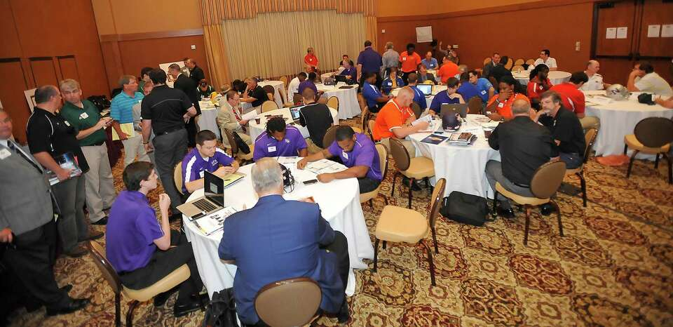 Coaches and players sit at their respective tables as the print media makes they way from table to t