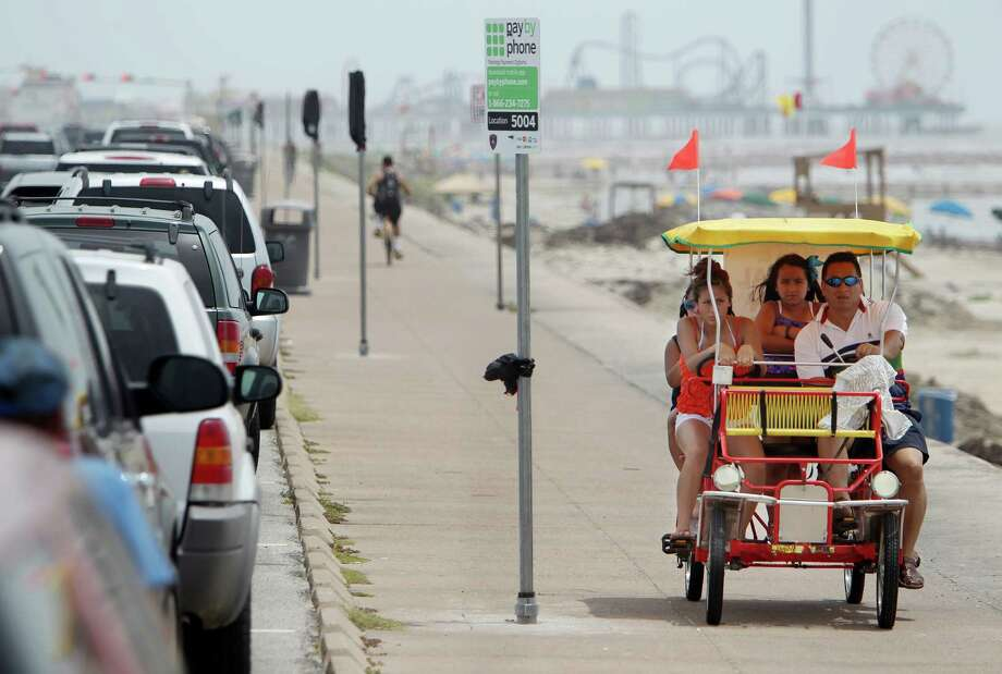 Vivi Fabian rides with her father, Jose, and sister Mia, of Dallas, on Wednesday along Seawall Boulevard, where signs have gone up to inform visitors about ways to pay for parking. Photo: Mayra Beltran, Staff / © 2013 Houston Chronicle