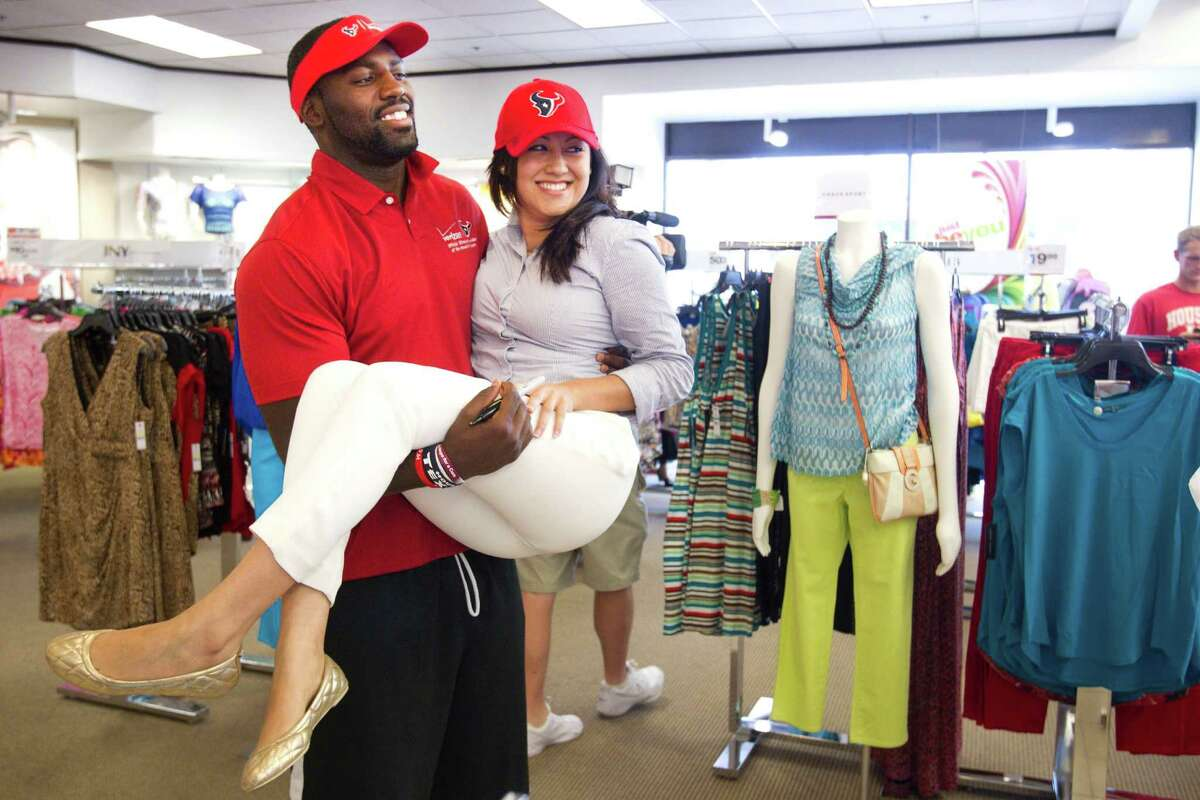 Houston Texans linebacker Whitney Mercilus carries Jessica Barrios as he poses for a photo during at stop at the Meyerland Palais Royal during the second Verizon Back to Football Care-A-Van Wednesday, July 24, 2013, in Houston. Texans players made visits to four locations throughout the Houston area to greet fans and sign autographs, as the team gets ready for the start of training camp.