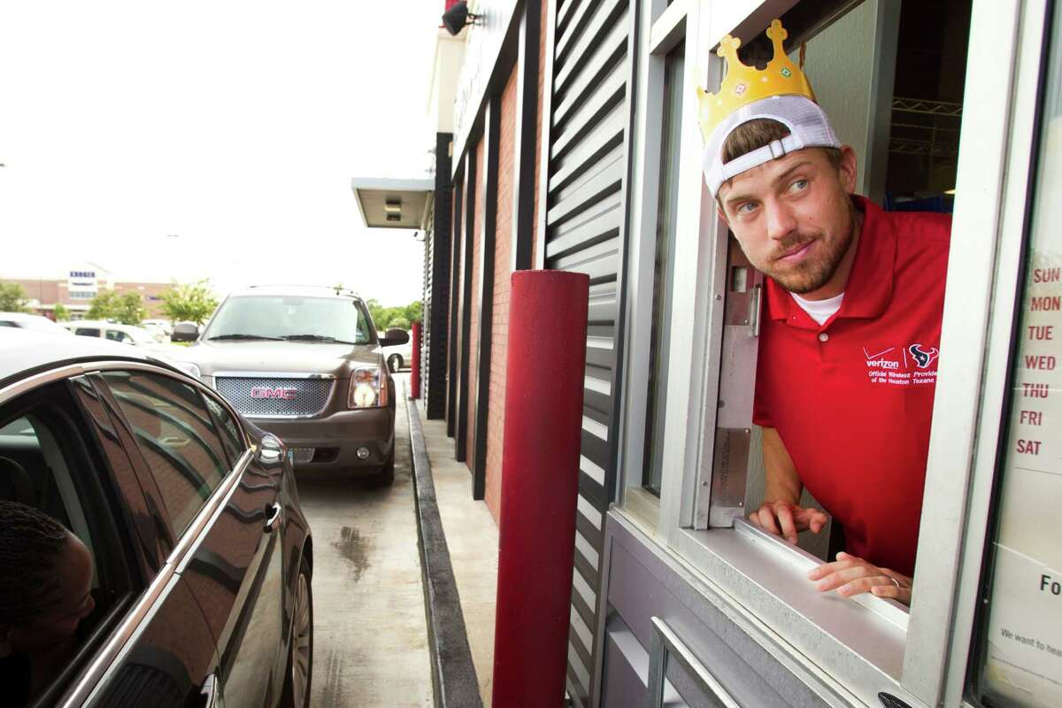 Houston Texans quarterback Case Keenum waits on a customer as he works the window at a Burger King during the second Verizon Back to Football Care-A-Van Wednesday, July 24, 2013, in Missouri City.