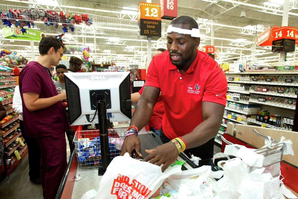 Houston Texans linebacker Whitney Mercilus, right, helps bag groceries at an HEB during a stop of the second Verizon Back to Football Care-A-Van Wednesday, July 24, 2013, in Pearland.