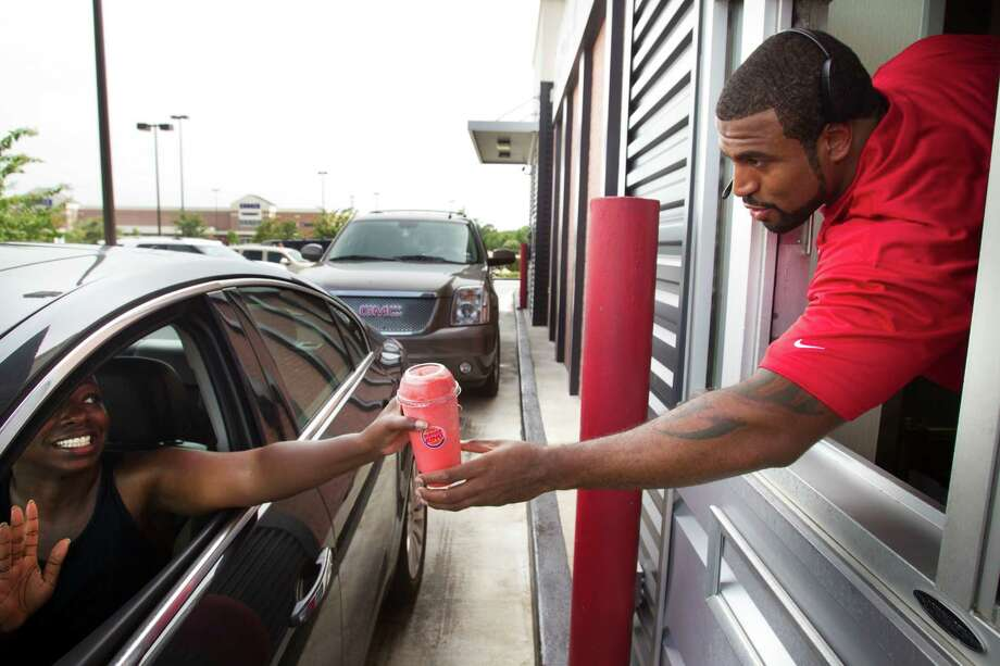 Houston Texans tackle Duane Brown, right, hands an ICEE to Tamika Prince as he works the window at a Burger King during the second Verizon Back to Football Care-A-Van Wednesday, July 24, 2013, in Missouri City. Photo: Brett Coomer, Houston Chronicle / © 2013 Houston Chronicle