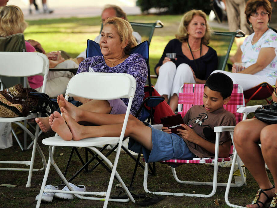 Andrew Guerra, 11, plays his Nintendo 3DS as his grandmother Orietta Caraballo looks on before the start of the show during Jazz Up July at Columbus Park in Stamford on Wednesday, July 24, 2013. Hearst Connecticut Newspapers are a sponsor of the event. Photo: Jason Rearick / Stamford Advocate