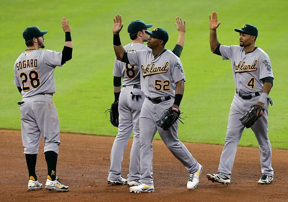 Eric Sogard (left), Jed Lowrie, Yoenis Céspedes and Coco Crisp celebrate after the A's took two of three from the Astros. Photo: Patric Schneider, Associated Press