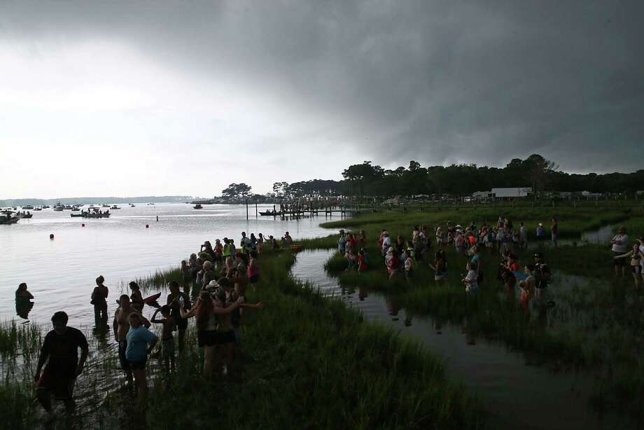 People stand in the marsh as a storm appoaches, while waiting for the wild ponies in their annual swim from Assateague Island to Chincoteague on July 24, 2013 in Chincoteague, Virginia. Every year the wild ponies are rounded up on the national wildlife refuge to be auctioned off by the Chincoteague Volunteer Fire Company. Photo: Mark Wilson, Getty Images / 2013 Getty Images
