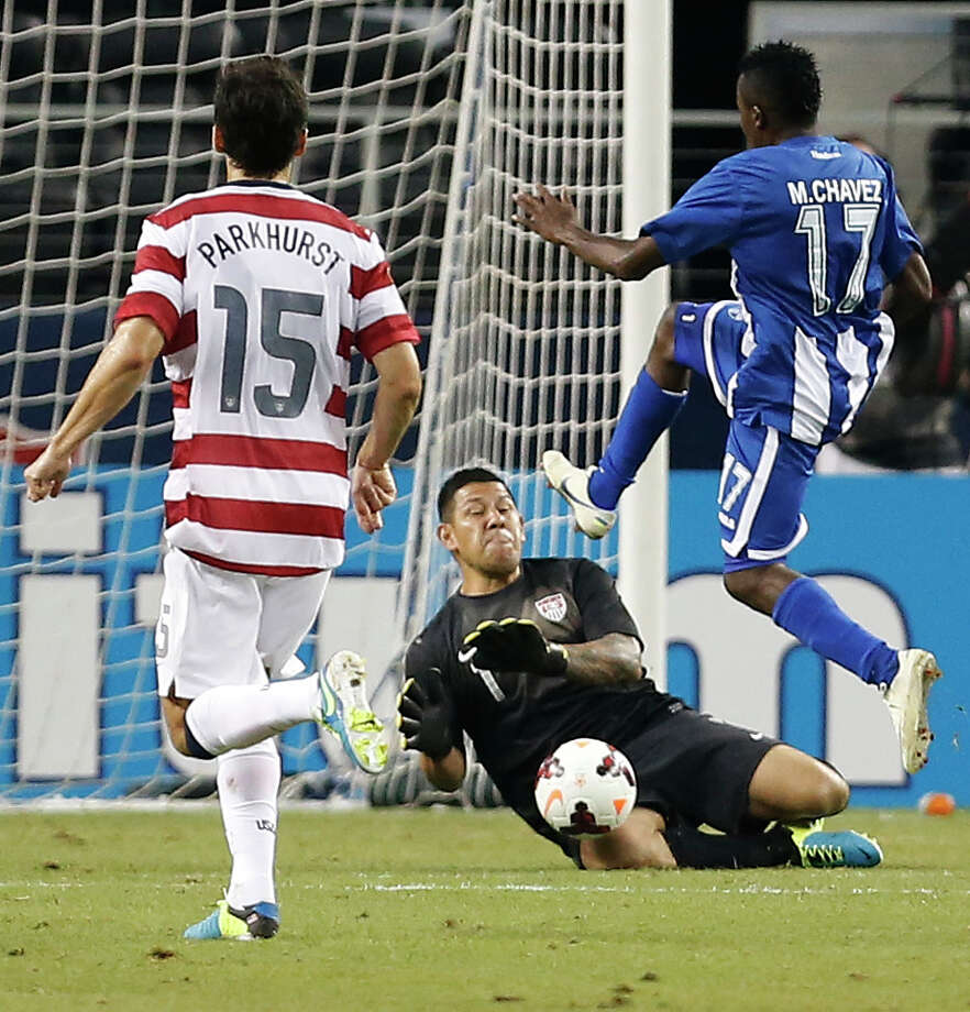 United States' Michael Parkhurst (15) looks on as teammate and goalkeeper Nick Rimando (1) blocks a shot by Honduras' Marvin Chavez (17) during the second half of the Gold Cup semifinals at Cowboys Stadium, Wednesday, July 24, 2013, in Arlington, Texas. The United States won 3-1. (AP Photo/Brandon Wade) Photo: Brandon Wade, Associated Press / FR168019 AP