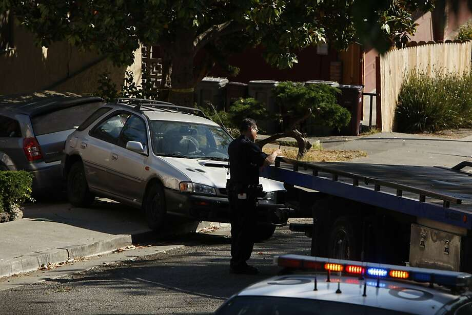 A police officer investigates at the scene where the slaying victim's car crashed after she was shot while driving near her home. Photo: Rohan Smith, The Chronicle