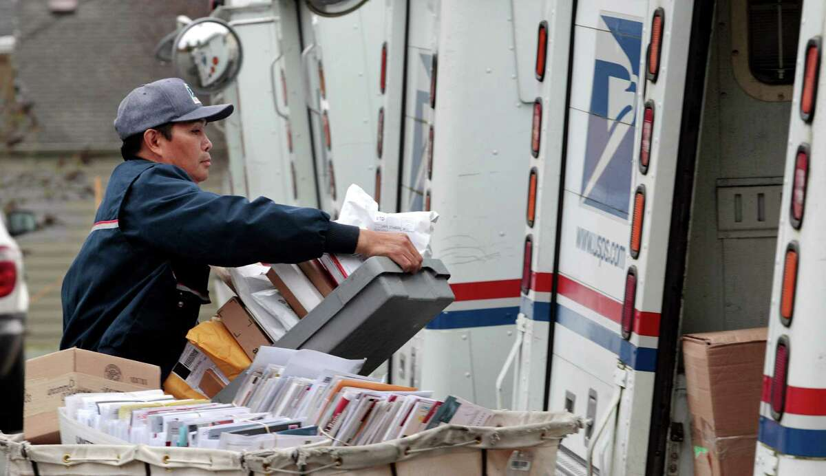 FILE - This Dec. 5, 2011 file photo shows a letter carrier moving boxes of mail into his truck to begin delivery at a post office in Seattle. (AP Photo/Elaine Thompson, File) ORG XMIT: WX101