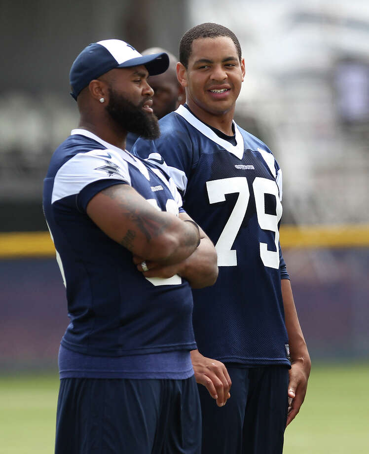 Injured player Anthony Spencer (left) and defensive end Ben Bass (79) chat during the morning session of the 2013 Dallas Cowboys training camp on Wednesday, July 24, 2013 in Oxnard. Photo: Kin Man Hui, San Antonio Express-News / ©2013 San Antonio Express-News