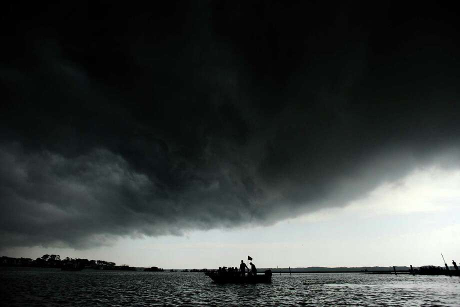 A boat in Assateague Channel is dwarfed by a thunderstorm cloud just before the Chincoteague Ponies hit the water for their annual swim to Chincoteague, Va. on Wednesday, July 24, 2013. The storm brought heavy rain as the ponies made the 88th annual swim. Photo: Jay Diem, Associated Press / Eastern Shore News