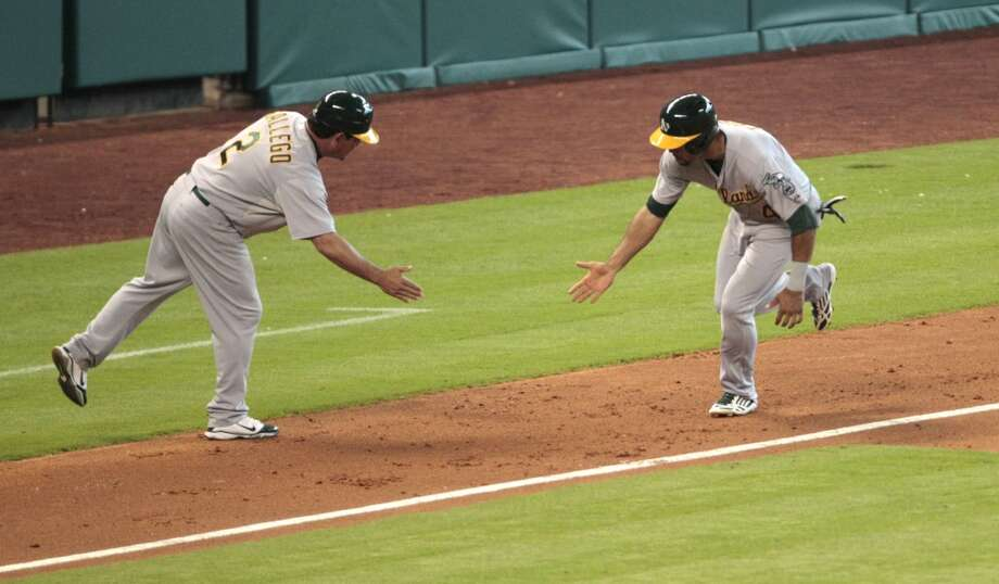 Coco Crisp rounds the bases  as he celebrates with third base coach Mike Gallego after his home run in the seventh inning. Photo: Billy Smith II, Chronicle