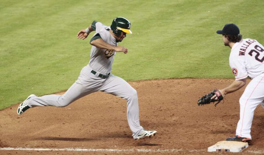 Coco Crisp grounds out as Brett Wallace catches the throw. Photo: Billy Smith II, Chronicle
