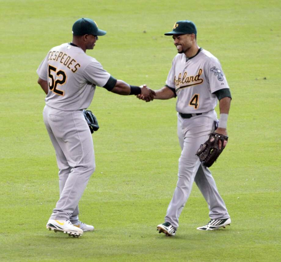 Yoenis Cespedes and Coco Crisp celebrate after the A's defeated the Astros. Photo: Billy Smith II, Chronicle