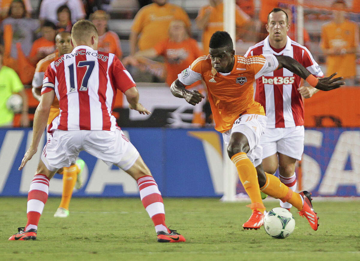 The Houston Dynamo's Jason Johnson 2nd from right, kicks the ball past Stoke City's Ryan Shawcross left, during the first half of the BBVA Compass Dynamo Charities Cup match at BBVA Compass Stadium Wednesday, July 24, 2013, in Houston.
