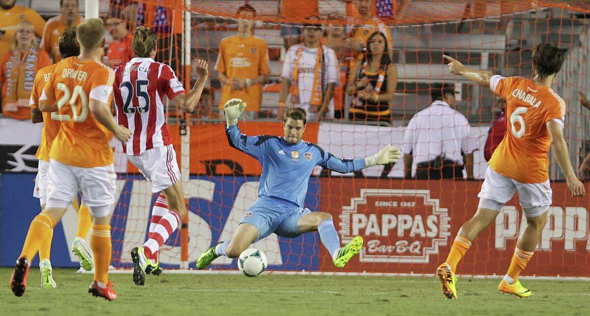 The Houston Dynamo's goal keeper Tyler Deric center right, blocks a shot by Stoke City's Peter Couch center left, during the first half of the BBVA Compass Dynamo Charities Cup match at BBVA Compass Stadium Wednesday, July 24, 2013, in Houston.